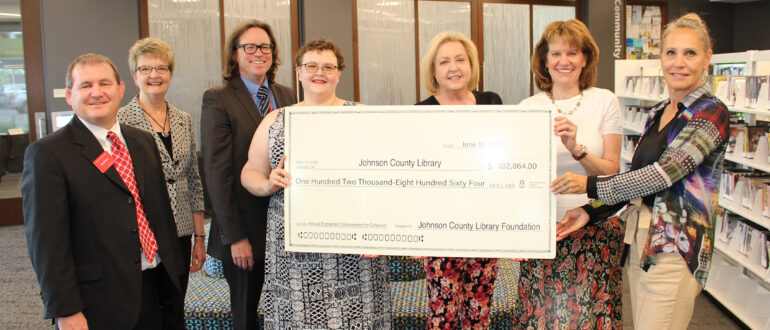 Johnson County Library Foundation Board members presenting a large check for the endowment of the Johnson County Library Collection in the total of $102,864.